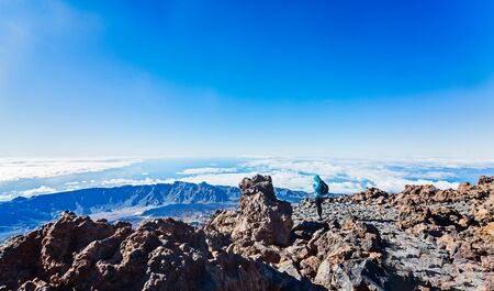 Woman using phone on the top of Teide volcano, the highest Spanish mountain. Tenerife. Canary Islands