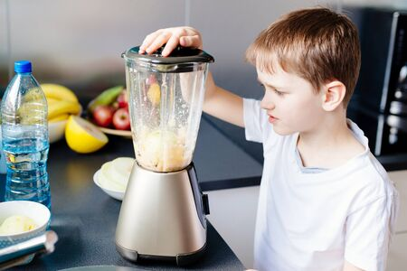 Little child boy mixing fresh fruits in blender. Preparing fruit cocktail or smoothie for breakfast. Healthy eating