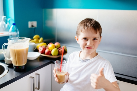 Happy little boy is drinking selfmade fruit cocktail. Healthy eating