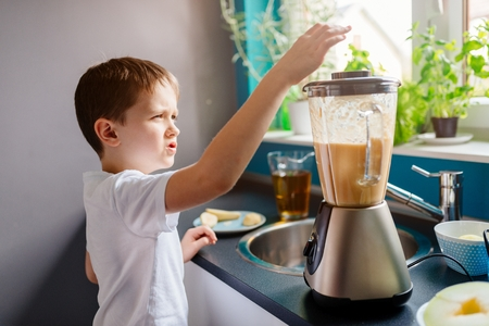 adding: Little child boy adding piece of melon to blender. Preparing fruit cocktail or smoothie for breakfast. Healthy eating