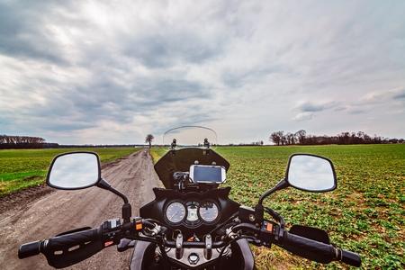 Motorradcockpit auf der unbefestigten Straße. Erste Person Ansicht