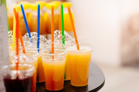 Tasty cold orange juice in plastic cup with straw