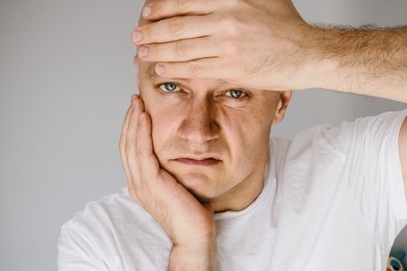 Man in white t-shirt suffers from toothache. Swollen face Stok Fotoğraf