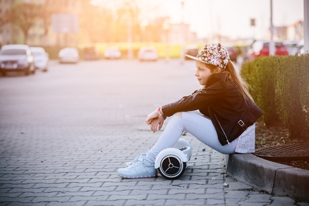 10 years old girl with self balancing electric skateboard - an electrical scooter