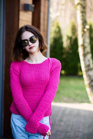 warm cloth: Portrait of young happy woman on terrace. Wearing pink knitted sweater Stock Photo