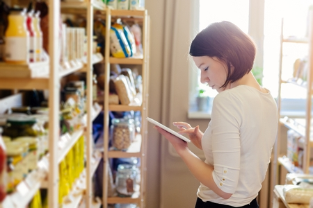 Woman owner of small local grocery store with healthy food ordering products using a tablet. Small Business Concept