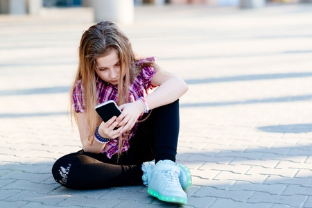 Portrait of happy blond hair ten years girl using smartphone