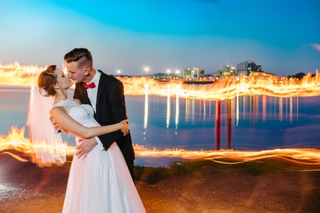 a meeting with a view to marriage: Newlyweds by the lake at night. Fire rays. Wedding day. Wedding session