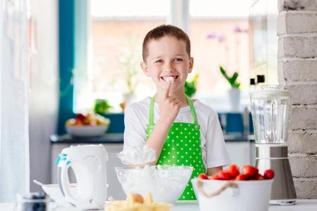 Child preparing sweet dessert and snacking whipped cream Reklamní fotografie