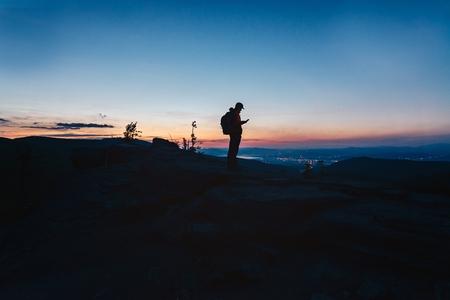 Man tourist standing on top of hill and using his smartphone. Malinowska Skala. Szczyrk. Silesian Beskid, Poland Stock Photo