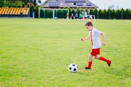 8 years old boy child playing football on playing field. Child playing football Stock Photo