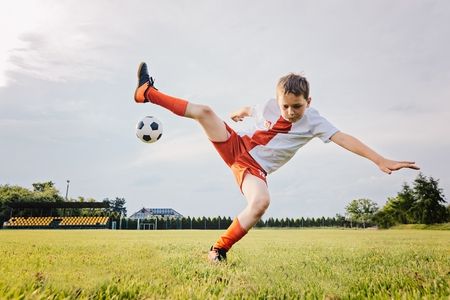 8 years old boy child playing football and rolls over after foul. Child playing football Stock Photo