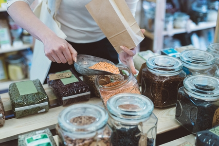 Woman puts lentil seeds into a paper bag in a healthy food store Standard-Bild