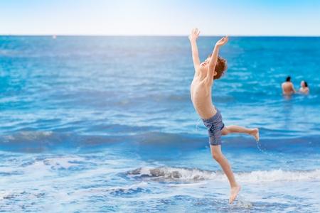 Gelukkig kind dat en op het strand springt speelt. Playa del Duque, Tenerife, Canarische eilanden, Spanje