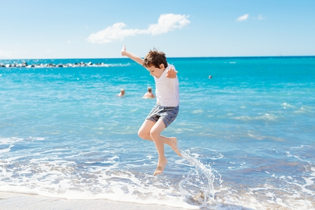 Happy child jumping and playing on the beach. Playa Del Duque, Tenerife, Canary Islands, Spain