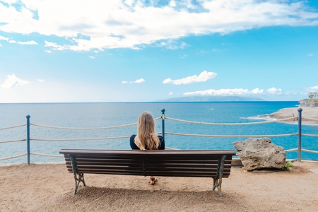 Woman sitting alone on the wooden bench in front of the ocean. Costa Adeje, Tenerife, Canary Islands, Spain