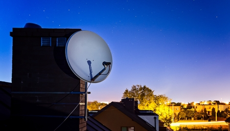 mounted: Satellite dish antenna mounted on the roof of the house at night