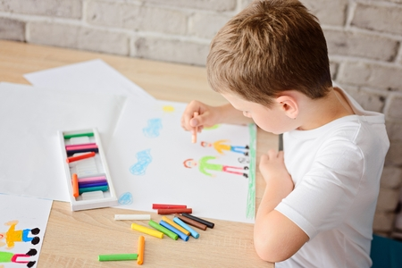 Child draws a drawing of happy son and father playing ball on meadow