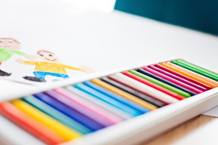 Colorful pastel oil crayons and childrens drawing of father with son Stock Photo