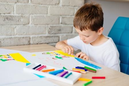 Il bambino disegna un disegno pastello di famiglia di olio sulla spiaggia. Wakacje - parola polacca per vacanze estive. Archivio Fotografico - 80377939
