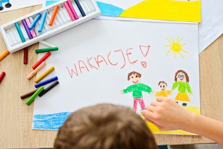 Il bambino disegna un disegno pastello di famiglia di olio sulla spiaggia. Wakacje - parola polacca per vacanze estive. Archivio Fotografico - 80377940