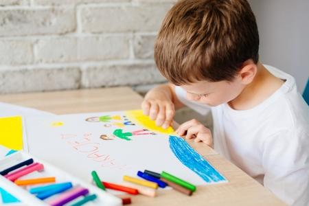 Il bambino disegna un disegno pastello di famiglia di olio sulla spiaggia. Wakacje - parola polacca per vacanze estive. Archivio Fotografico - 80377963