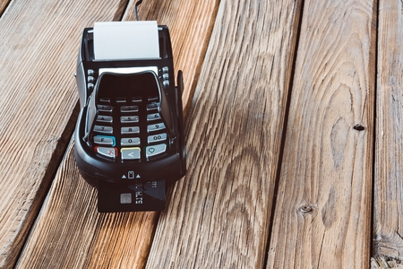 shopper: Payment with credit card terminal. Wooden background