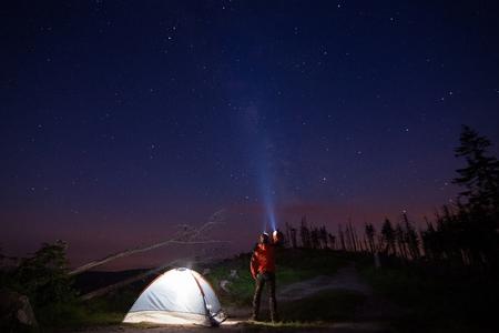 Man toerist die zijn zaklamp wijst naar de sterrenhemel in de nacht. Malinowska Skala. Szczyrk. Silezische Beskid, Polen