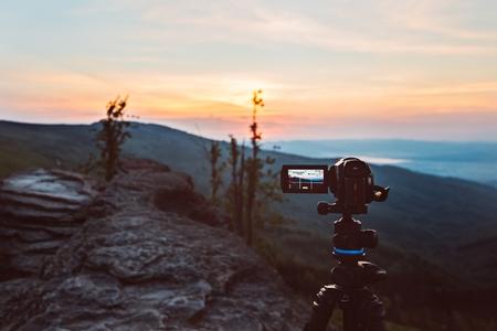 Digital video camera on tripod filming sunrise at mountains. Silesian Beskid, Poland