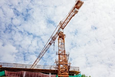 realestate: Working crane and building under construction against blue sky