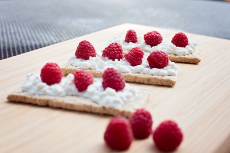 Crunchy rye-wheat bread with white cottage cheese and raspberries. Delicious diet healthy snack.