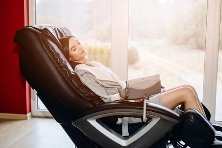 Joven relajante en la silla de masaje en casa