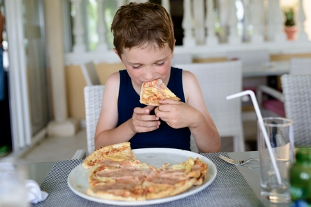 Boy eating delicious pizza. Child in restaurant