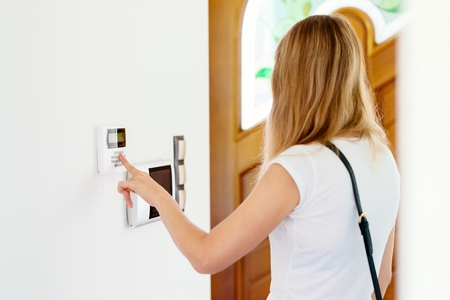 Young woman entering authorization code pin on home alarm keypad. Home security concept Stock Photo