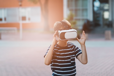 Little child boy watching simulation in virtual reality googles.