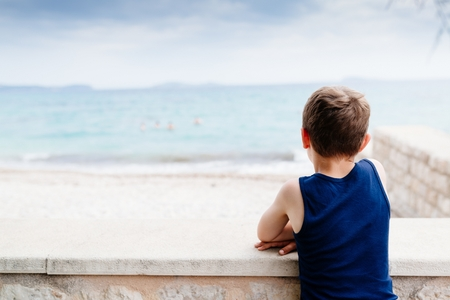 Thoughtful little boy on summer vacations at the sea