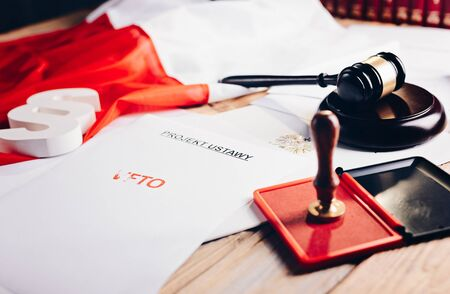 Red veto stamp on law act and Polish flag - law office concept