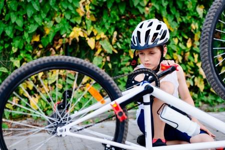 Happy boy in a bicycle helmet repairing his bike. Child on bike Stock Photo