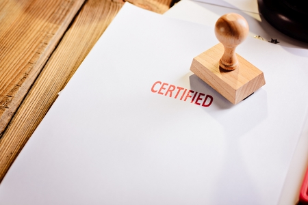 Red certified rubber stamp on white sheet of paper. Law office. Stock Photo