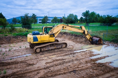 Yellow excavator on the tracks in the mud