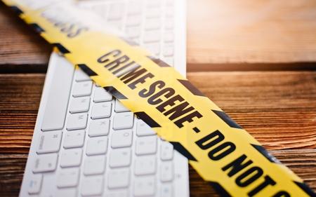 Yellow crime scene tape on computer keyboard. Computer crime concept. Zdjęcie Seryjne