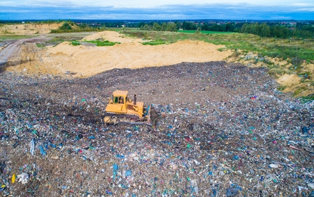 Aerial view on bulldozer working on the landfill. Environmental pollution
