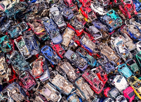 Destroyed scrapped cars stacked on a scrap yard. Car recycling