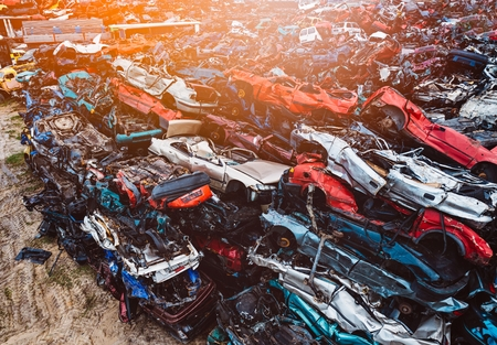 Destroyed scrapped cars stacked on a scrap yard. Car recycling Banco de Imagens