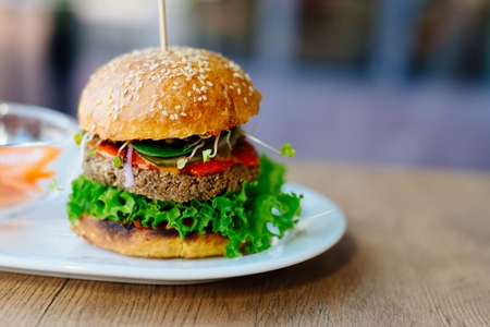 Delicious Mexican vegan burger with chickpeas, onion, lettuce and spicy chili sauce Stok Fotoğraf