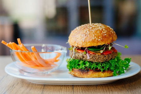 Delicious Mexican vegan burger with chickpeas, onion, lettuce and spicy chili sauce Archivio Fotografico