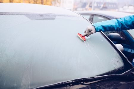 女性が車のフロント ガラスからガラス スクレーパーと氷を除去します。凍りつくような朝