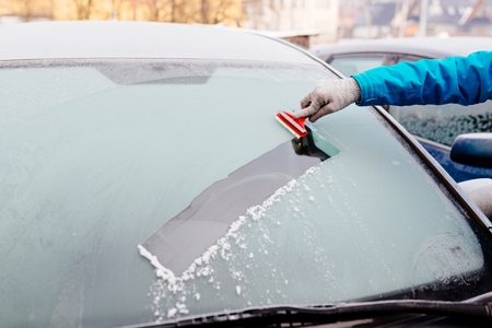 Woman removing ice from car windshield with glass scraper. Frosty morning