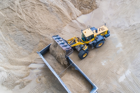 Yellow wheel loader loading sand on dumper truck. Sand quarry