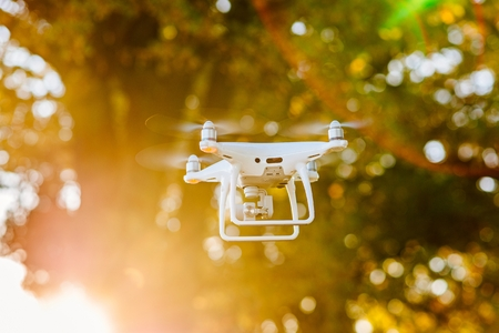 White drone quadcopter with camera in flight Stock Photo